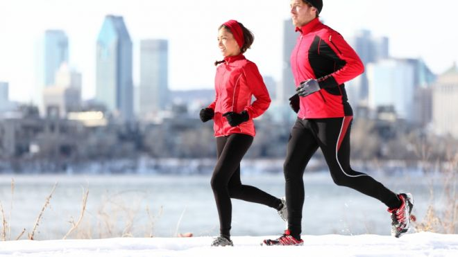 man and woman running in snow