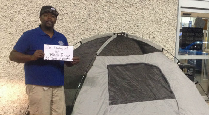 Kevin Sutton holding sign at Best Buy