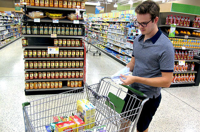 man checking grocery coupons