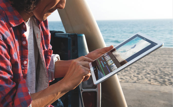 Person using iPad Pro by beach