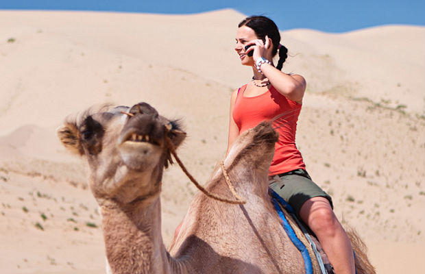 woman on phone while riding camel