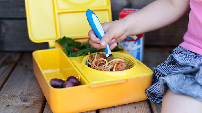 child eating from lunch box